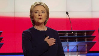 Hillary Clinton sings along to the national anthem before the start of a CNN Democratic debate on March 6, 2016, in Flint, Michigan.