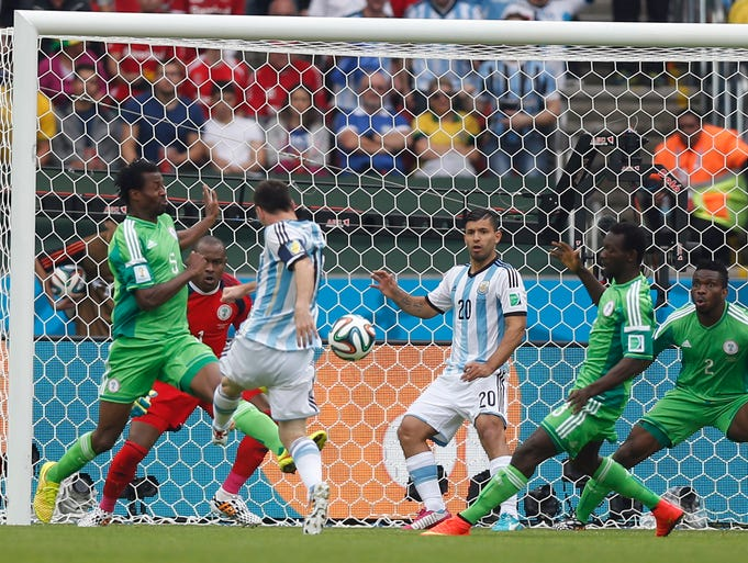 Argentina's Lionel Messi, third left, scores the opening goal during a group F World Cup soccer match between Nigeria and Argentina at the Estadio Beira-Rio in Porto Alegre, Brazil, Wednesday, June 25, 2014.