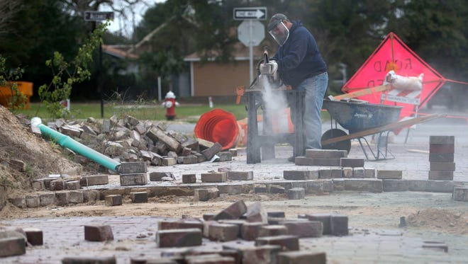 Emerald Coast Utilities Authority employee, Rocky Boyd, works on reclaiming brick pavers for reuse on LaRua Street Thursday morning Jan. 7, 2015. A portion of the downtown Pensacola street has been in disrepair and Impassable for nearly a year.
