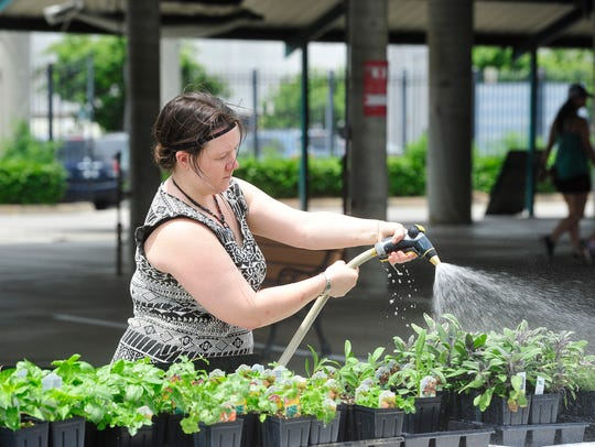 Melissa Beavers of Further Farms waters her plants
