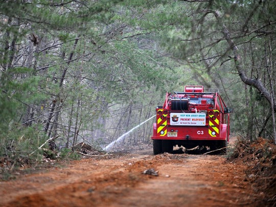 A NJ Forest Fire Service brush truck sprays a hot spot