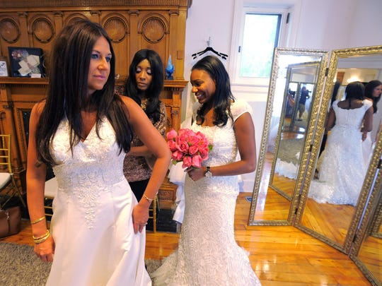 Keasha Rigsby, center, the co-owner of Beautiful Bridal, helps Elizabeth Pensler, left, of Beverly Hills, and Yana Gaines of West Bloomfield, with their dresses.