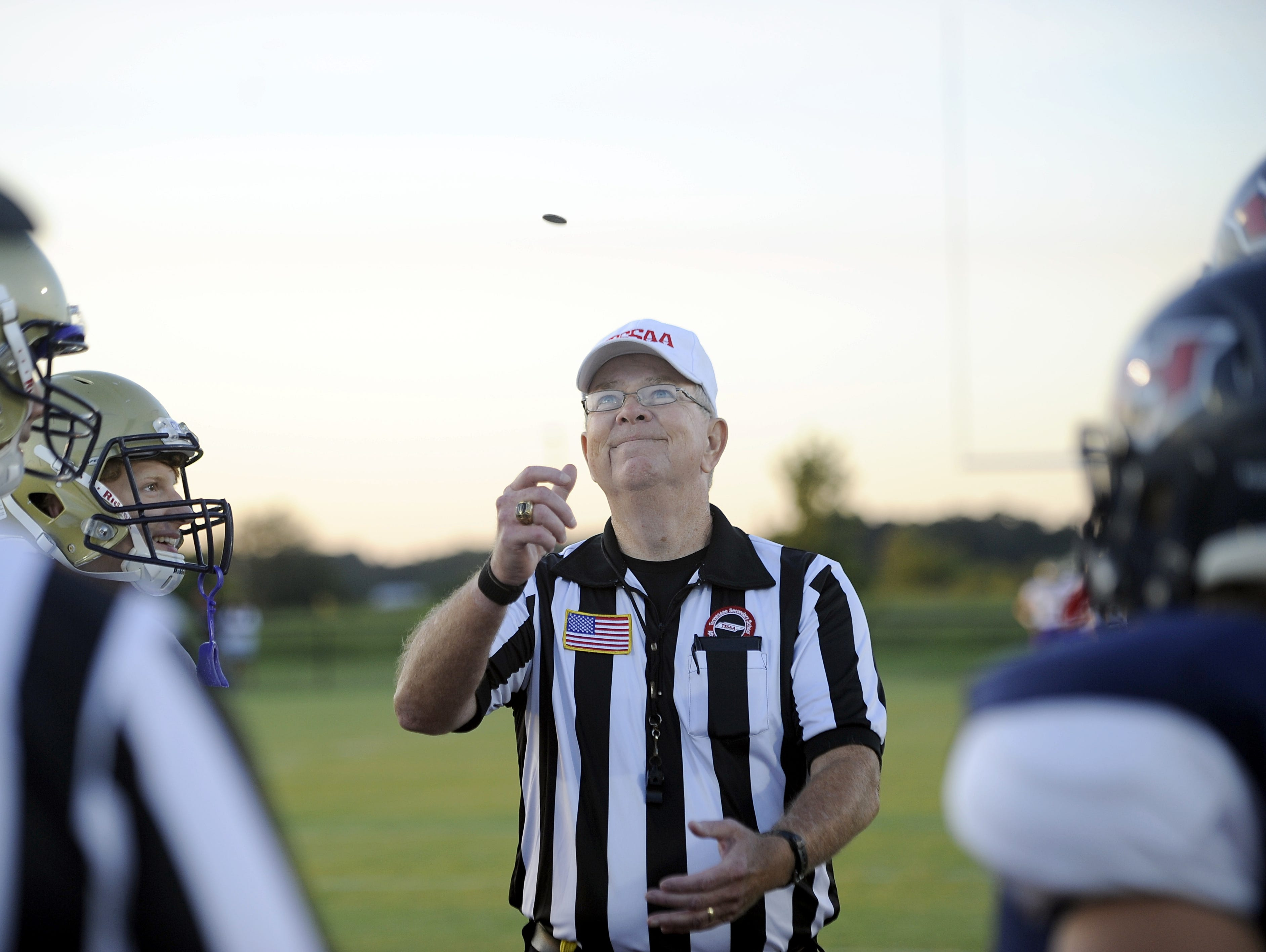 Referee Jody Swearingen of the North Middle Football Officials Association flips the coin prior to a game between Christ Presbyterian Academy and White House-Heritage.