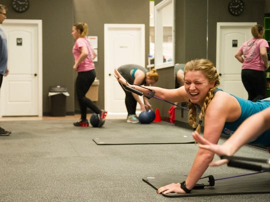 Brittany Schnaare, right, laughs as she does superman pushups with her friend, Kaitlyn Eckart (not pictured) during a high intensity interval class at Shed Fitness.