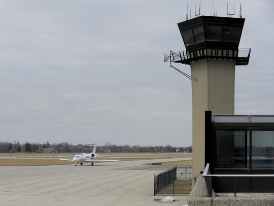 A plane taxis past the Detroit City Airport tower in