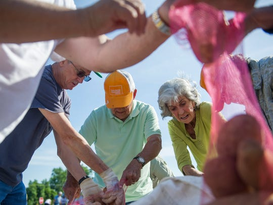 Volunteers separate potatoes into ten pound bags at
