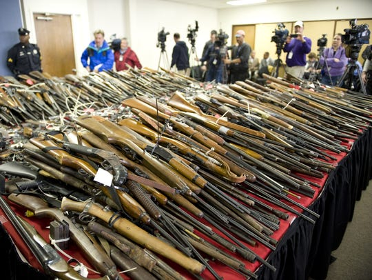Guns obtained by Camden County Police are stacked on