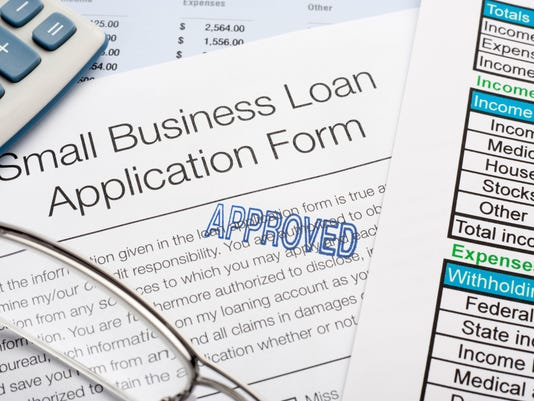 Approved Small Business loan application Form with pen, calcula