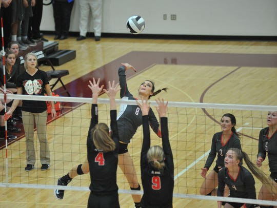 Lexi Evak spikes one over two St. Paul defenders at the net in the district championship.