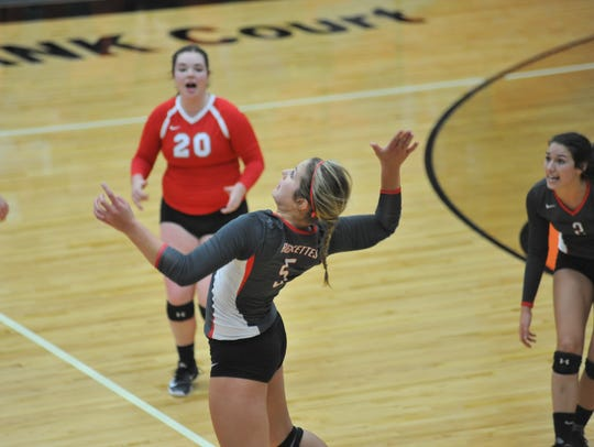 Jenna Karl goes up for a kill with Bailey Agin looking on.