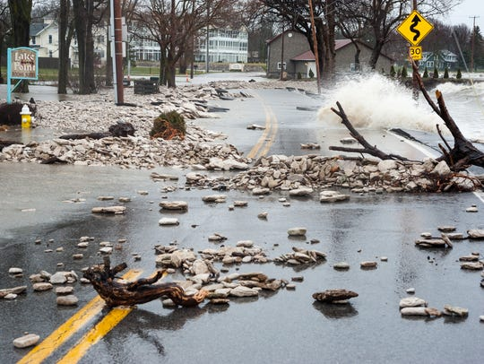Waves carrying debris crash over East Bayshore Road