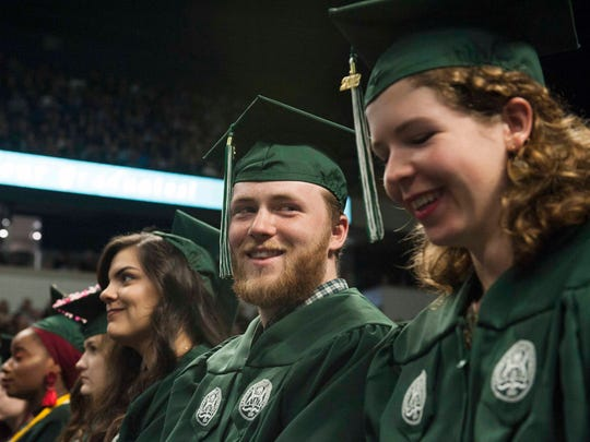 EMU graduates Emilee Lopez, left, of Clinton Township, Maximilion Fraleigh of Ann Arbor and Anthea Van Geloven of Ann Arbor smile during the ceremony.