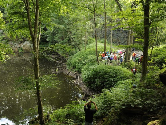 A tour group of more than 50 bikers stops near the quarry/railroad cut along the Blackhand Gorge bike path .