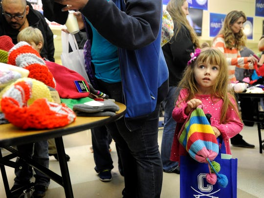 Aubree Lotspeich, 3, holds onto a hat her mother gave her off a table filled with free hats for students and their families during the Chillicothe City School District's Community Day on Tuesday. Families of students were invited to come to the school to get a free tote bag, canned goods, books, hat, gloves, dinner, haircut, picture with Santa and more.