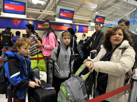 Toby Lewis, 34, and her two boys, Casey, 12, and Ian, 10, from Ann Arbor, wait in line at the Delta counter in the McNamara Terminal at Detroit Metropolitan Airport in Romulus, Michigan on November 26, 2014.  They are traveling to Massachusetts to visit her mother.