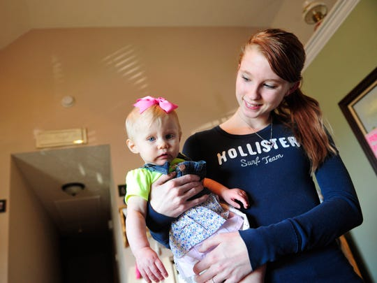 Ashley Rochester holds 7-month-old River DeBoard in