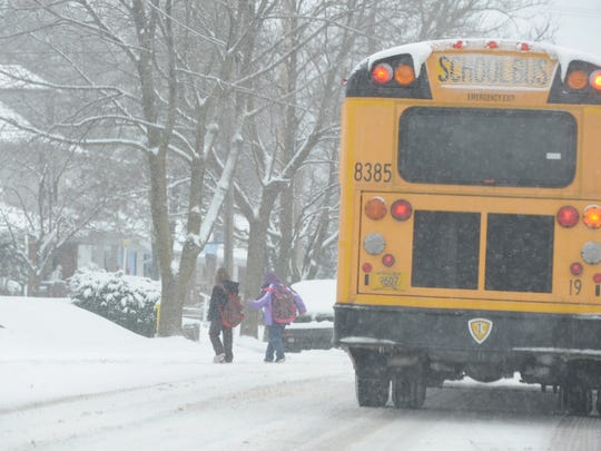 Students cross the street after exiting a Richmond school bus.