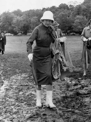 It was a day for boots and determination at the 17th running of the Iroquois Steeplechase and Mrs. John B. Wilson, 4115 Harding Road, plods her way through the mud to a seat on May 11, 1958.