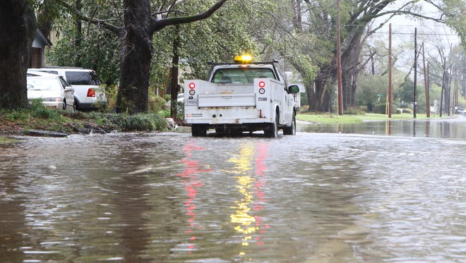 A Monroe Public Works Department truck stops near the intersection of Fifth Street and Hilton Street on Wednesday. Public Works Department employees unclogged drains along the flooded streets to allow the water to drain faster.
