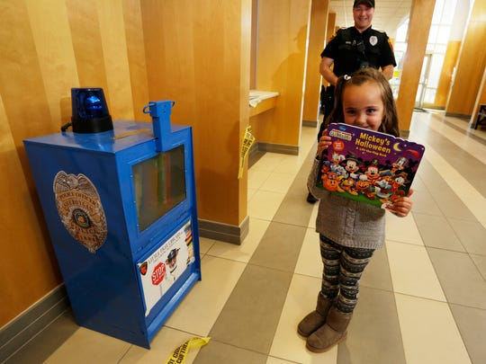 Sheboygan Police Officer Matthew Heimerl, background, stands as his daughter Briella, 5, holds a book from the little free library that was created from a Sheboygan Press paper box, Wednesday, October 18, in Sheboygan. Heimerl noticed the proliferation of small libraries in the city while on duty. He felt it was a way to encourage reading for children if they happen to visit the station with their parents.