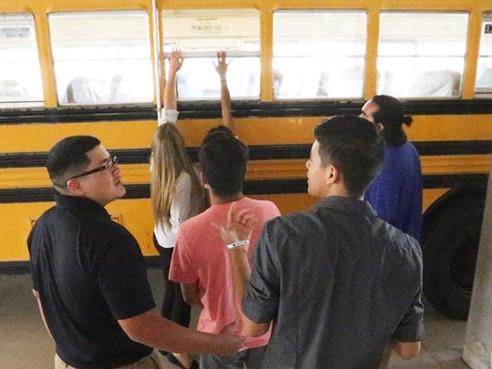 Students in the Bowie High School Business Academy show a donated district school bus that they plan to turn into a food truck at the South El Paso school Wednesday.