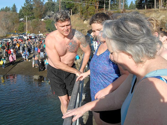 From left, Marquis and Heather Pounds of University Place get set to jump with Mary Fleming of Olalla. Fleming, who is 70, made her first-ever Polar Plunge.