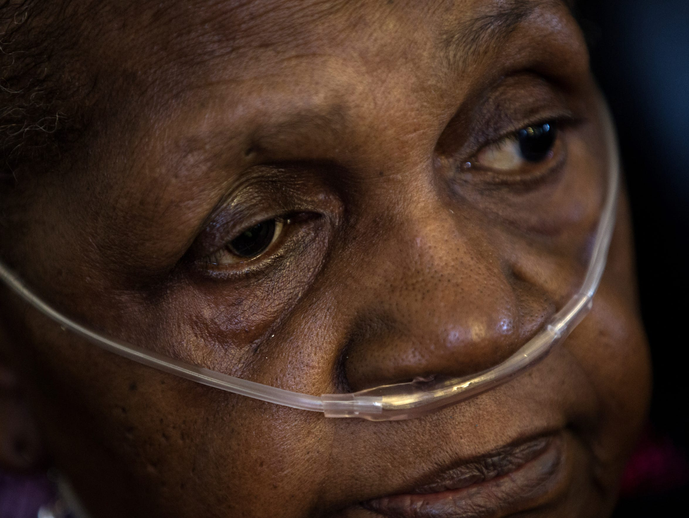 "Gloria McPhail, 73, sits in her living room in Detroit's Delray neighborhood on July 12, 2017. She requires an oxygen tank to breathe.  She was considering taking the city's offer of a new home in another Detroit neighborhood. ""Well, one reason I want to do it is for my health. My health is getting worse. My breathing is getting worse,"" she said."
