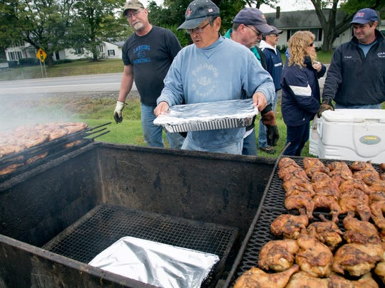 Steve Kuramoto, of Lansing, loads a tray of baked beans into the grill to get them warmed up. Kuramoto was one of the fathers of Lansing High School seniors helping Hatfield on Friday.