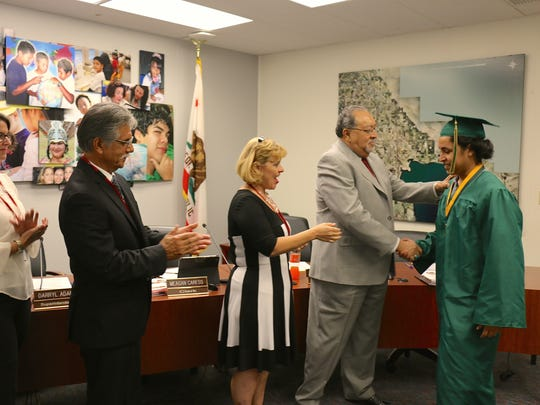 A 2015 summer graduate student from Coachella Valley High School is congratulated by district board members at last year's commencement ceremony.