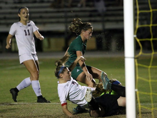 Estero captain Haley DeSanto (7) dives into a dropped save from Venice goalkeeper Ashton Pennel during the Region 4A-3 quarterfinals against Venice. The Wildcats host Bloomingdale on Tuesday in a regional final.