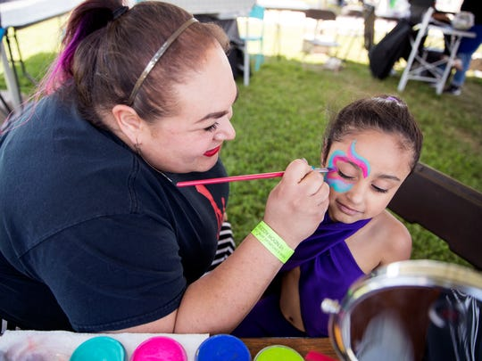 Monica Garcia (left) paints Emma Varughese', 5, of Houston, face during day two of Fiesta de la Flor on Saturday, April 14, 2018.