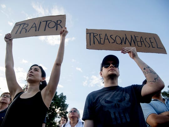 People hold signs during a protest outside the White House on July 17, 2018, in Washington. It was the second day of protests following President Donald Trump's meetings with Russian President Vladimir Putin.