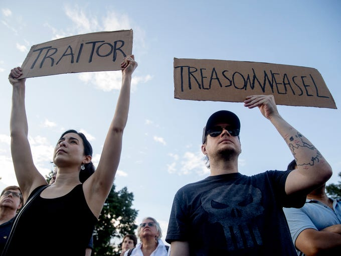 People hold signs during a protest outside the White