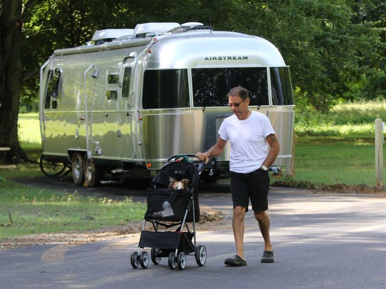 Frank Vito, of Ocean City, Md., takes a walk with his 18 year-old Sheltie Holly around Lums Pond State Park Campground where he was camping Friday. The campground just underwent several improvements for visitors including fresh paved roads.