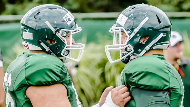 MSU offensive lineman Jack Allen, left, prepares for a blocking drill with his brother, Brian Allen, during a summer camp practice on August 6, 2014. Matt Allen, the younger brother of the two, has committed to Michigan State.