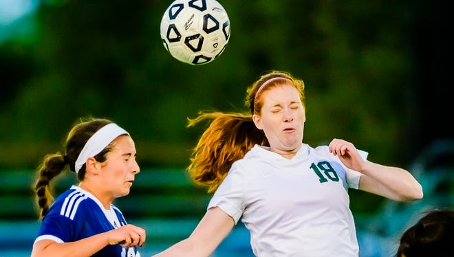 Megan Mowid ,left, of Haslett and Malorie Christie of Wiiliamston fight for position on the ball during their CAAC Gold Cup final game Thursday