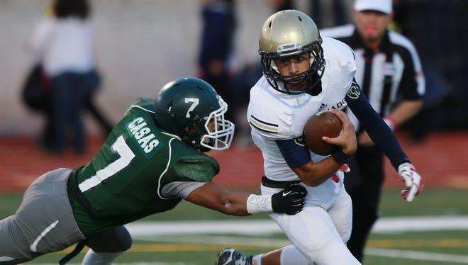 Coronado quarterback Angelo Donatelli, right, evades a tackle attempt by Montwood's Brandon Casas.