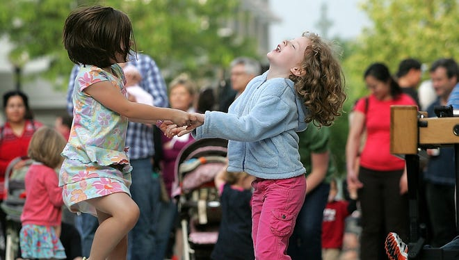 Ella Hackathorn, 5, left, and Alice Boerner, 6, both of Iowa City, dance to the music as the West High Jazz Band gives the first performance of the 2010 Friday Night Concert Series on May 21, 2010, on the pedestrian mall in downtown Iowa City.