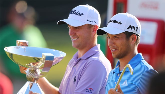 Justin Thomas, left, holds the trophy after winning the Fedex Cup, as he stands with Xander Schauffele, who claimed the Tour Championship Sunday at East Lake Golf Club in Atlanta.