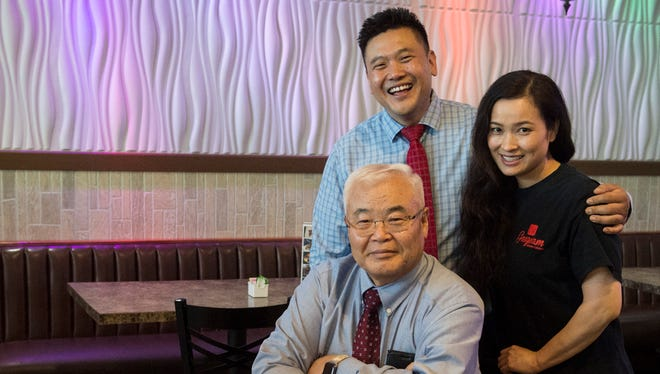 Joe Kim, top left, poses for a photo with his father, Suk Ki, and his wife Sarah at Gangnam restaurant in Owensboro, Ky. on Wednesday, May 30, 2018.