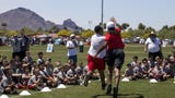 Arizona Republic's Greg Moore takes on Cardinals wide receiver Larry Fitzgerald after the youth football clinic in Fitzgerald's name, held at the Salt River Fields on Saturday, April 21, 2018.