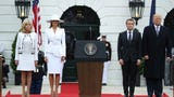 The first lady greeted French President Emmanuel Macron and first lady Brigitte wearing an all-white hat and matching suit ensemble.