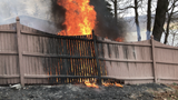 An outdoor fire gets out of control on a gusty afternoon along Greenwood Lake in New York. A fence and part of the neighboring lawn catches on fire.