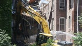Demolition crews begin the process of taking down damaged buildings on Academy Street in the City of Poughkeepsie following a partial collapse Monday afternoon.