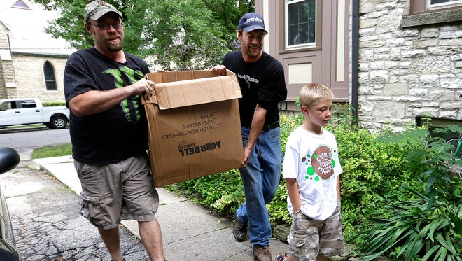 Tyler Nett and Ian Seth carry a box of donated merchandise to the Solution Center Friday that 8-year-old Owen Nett, front, helped pay for.