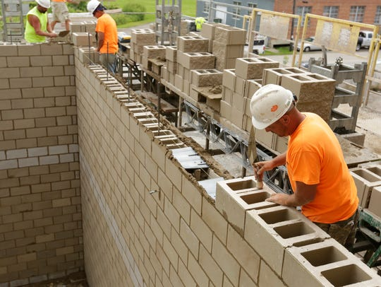 Brandon Clausen of Pahlow Masonry levels out a block