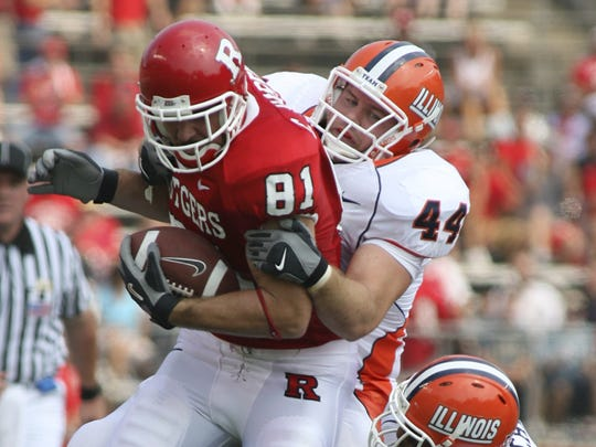 Former Southern standout Clark Harris fights off a pair of Illinois defenders during a 2006 game for Rutgers. Harris is in his eighth NFL season as a long-snapper.