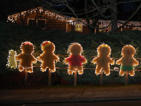 Gingerbread people line the sidewalk as part of one of the may Christmas displays along Viewcrest Drive NE neighborhood on Thursday, December 7, 2017.