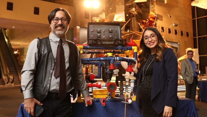 """Faridodin Lajvardi, the coach of the Carl Hayden high school robotics team, and Angelica Hernandez, an alumni, pose with the robot """"Stinky"""" at the Smithsonian Air and Space Museum on Feb. 15, 2017. The two were featured in the documentary """"Dream Big,"""" that had its premiere on the museum's IMAX screen."""