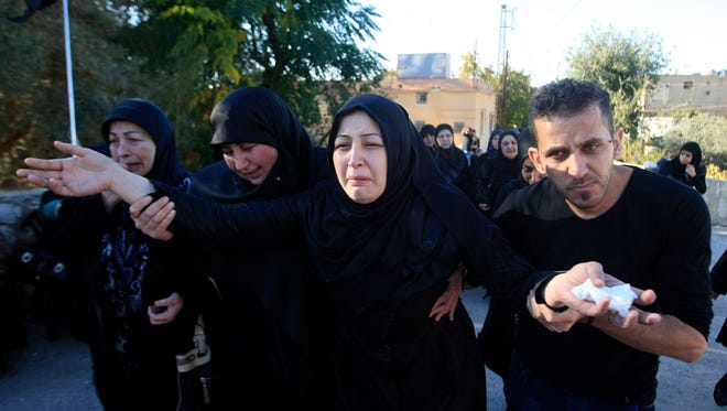 The wife of Adel Termos, who was killed in twin suicide bombings, mourns during his funeral procession in the southern Lebanese village of Tallousa, Lebanon, Friday, Nov. 13, 2015.